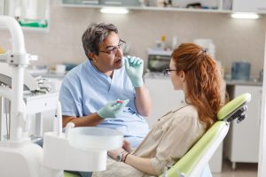 ddentist alking to young female patient about wisdom tooth impaction