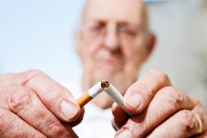 Older man snapping cigarette in half