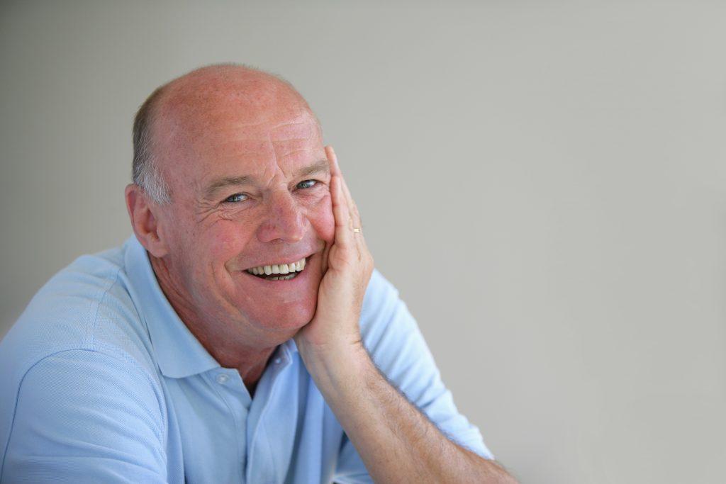older man smiling blue shirt