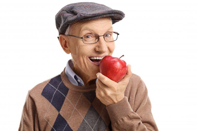 older man smiling eating apple