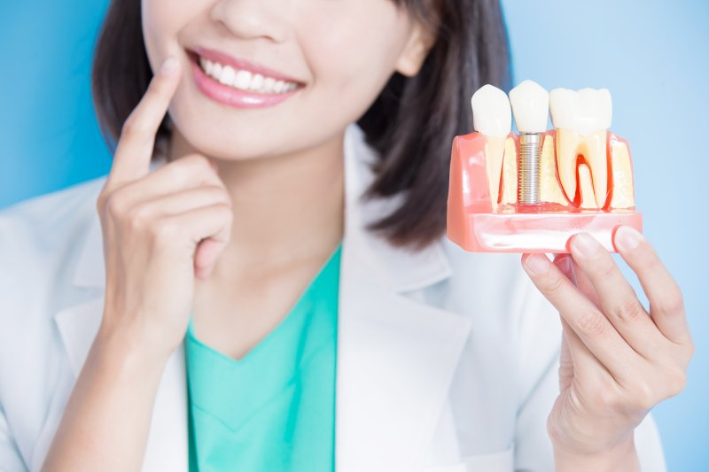 a woman holding a tooth mold with a dental implant and pointing to her mouth