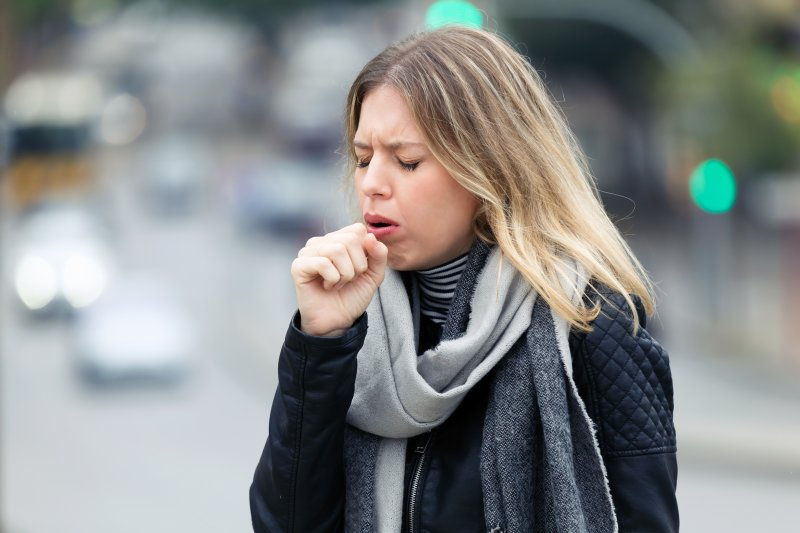 Young woman with scarf coughing on the street