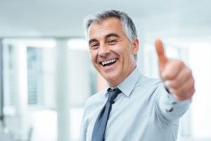 Cheerful businessman thumbs up posing and smiling at camera
