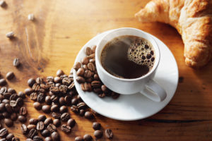 White cup of coffee on table surrounded by coffee beans