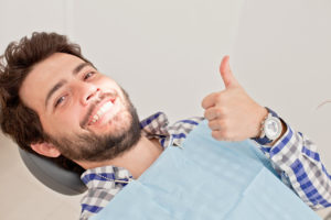 Young man in dental chair giving thumbs up